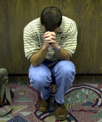 stranded traveler praying at airport
